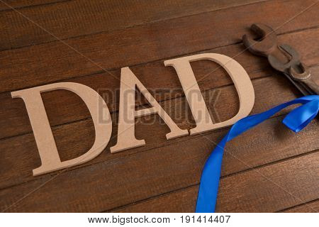 Close-up of decorated wrenches and text dad on wooden plank