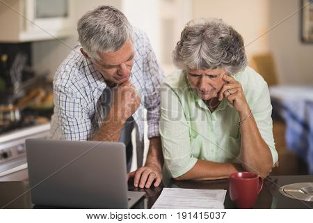 Serious senior cpouple reading documents by laptop on table at home