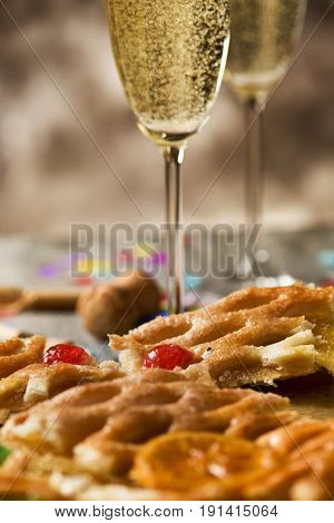 closeup of a coca de Sant Joan, a typical sweet flat cake from Catalonia, Spain, eaten on Saint Johns Eve, on a rustic table, a pair of glasses with champagne, firecrackers and confetti