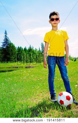 Happy boy plays football in the park. Summer holidays. Outdoor activities.