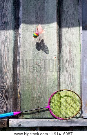 A ball on a nail and a badminton racket on a wooden wall with a shadow on a summer day