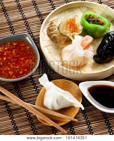 Assorted Dim Sum in Bamboo Steamed Bowl and Dai-Tory with Chiken on Wooden Plate with Red Chili and Soy Sauces and Chopsticks closeup on Straw Mat background