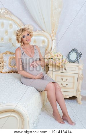 Portrait of a young pregnant woman touching her belly with hands sitting on the bed in a modern interior. Happy motherhood and pregnancy.