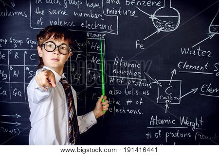 Smart schoolboy answering by a blackboard on a chemistry lesson. Educational concept.
