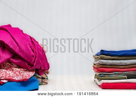 Pile of unfolded clothes beside a pile of folded clothes and space for text in the centre
