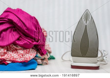 Pile of girls clothes next to an iron ready to be ironed.