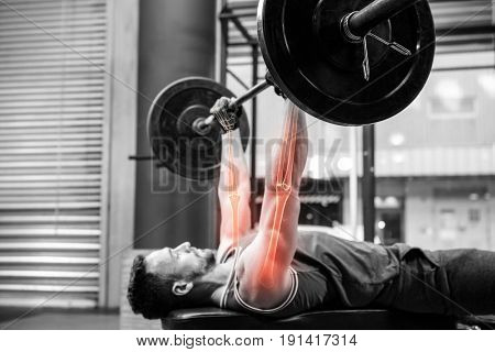Side view of dedicated sportsman athlete exercising with barbell at gym