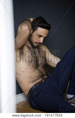 handsome hairy young man sitting shirtless on floor
