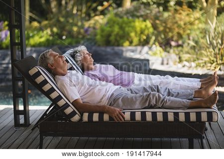 Full length of senior couple resting together on lounge chairs at porch