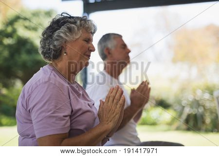 Side view of senior woman meditating with man meditating at porch