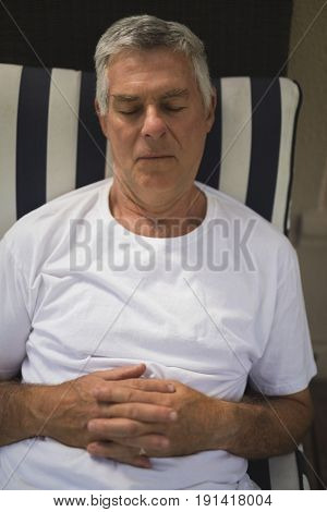 High angle view of senior man sleeping on lounge chair