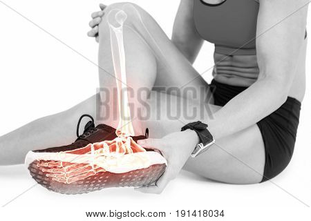 Low section of female athlete suffering from ankle pain while sitting on white background