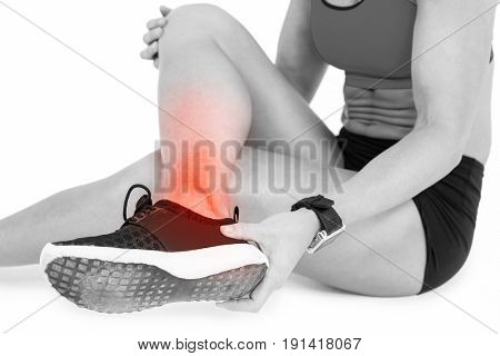 Low section of female sportsperson suffering from ankle pain while sitting on white background