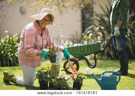 Portrait of smiling senior woman holding plant while kneeling on field in yard