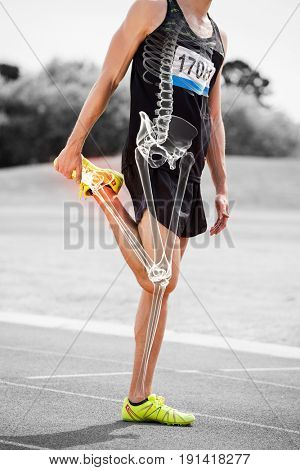 Digital composite of highlighted bones of athlete man stretching on race track