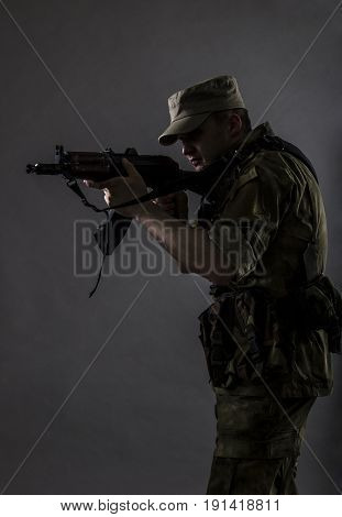 A military mistical portrait. The military man is standing with gun on sight.