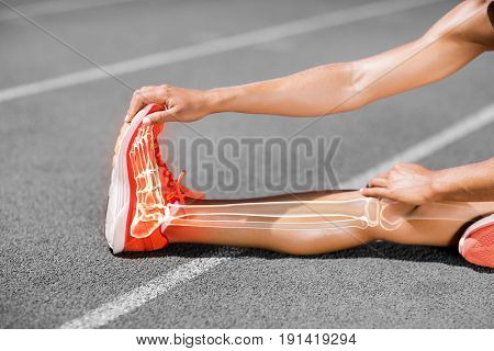 Low section of female athlete stretching on sports track during sunny day