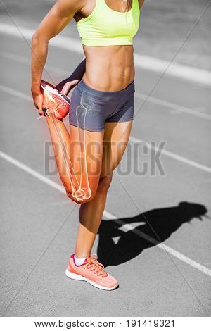 Low section of female athlete stretching leg on sports track during sunny day