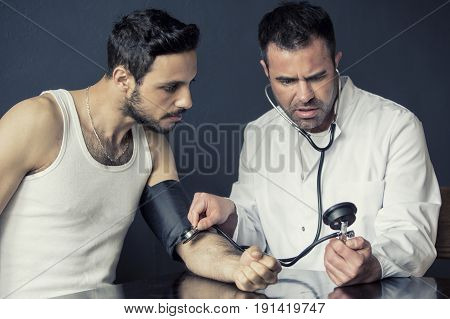 doctor with sphygmomanometer checking the pulse from handsome patient