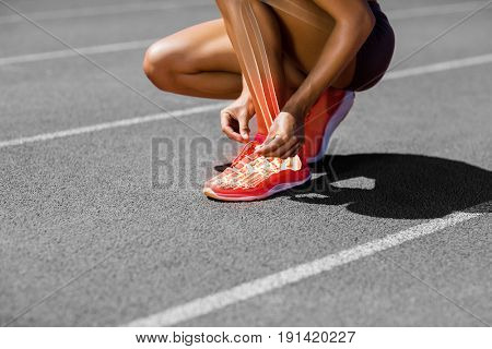 Low section of sportswoman tying shoelace on track