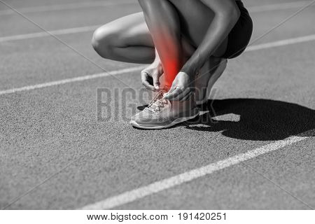 Low section of athlete tying shoelace on sports track during sunny day