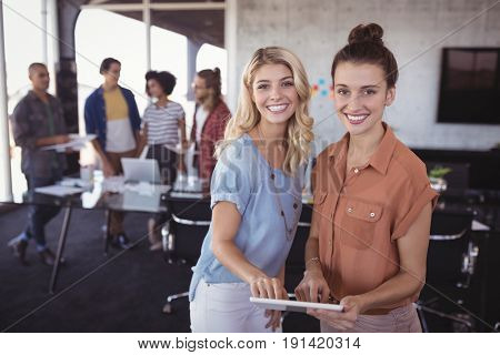 Portrait of happy businesswomen holding digital tablet with creative team in background