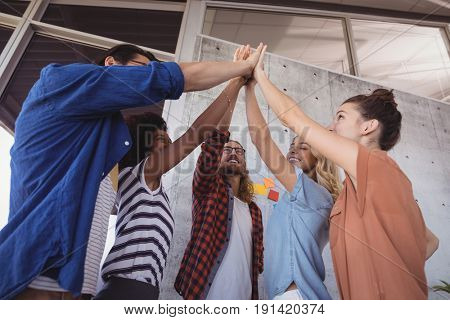Low angle view of cheerful business people giving high five in creative office