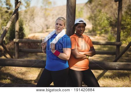 Portrait of happy friends standing with arms crossed during obstacle course in boot camp