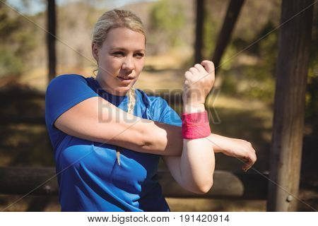 Beautiful woman performing stretching exercise during obstacle course in boot camp