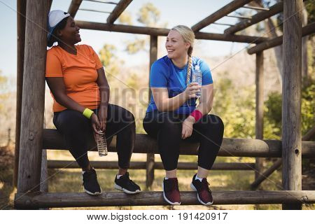Happy friends holding water bottle while relaxing in boot camp during obstacle course