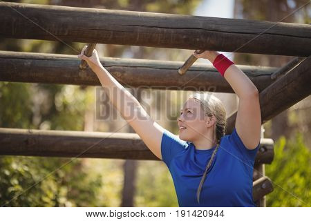 Determined woman exercising on monkey bar during obstacle course in boot camp