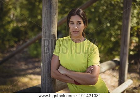 Portrait of confident woman leaning with arms crossed during obstacle course in boot camp