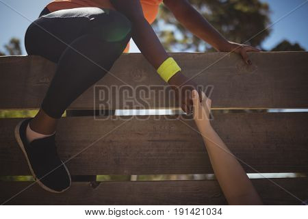 Trainer assisting woman in wooden wall climbing during obstacle course in boot camp