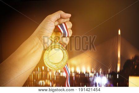 Businessman winner holding medals gold award for show celebration blur city light background
