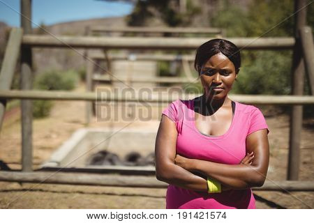 Portrait of woman standing with arms crossed during obstacle course in boot camp