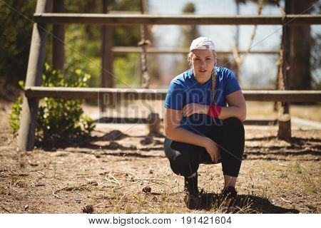 Portrait of confident woman crouching in boot camp during obstacle course