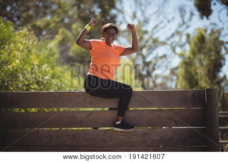 Portrait of happy woman cheering on wooden wall during obstacle course in boot camp