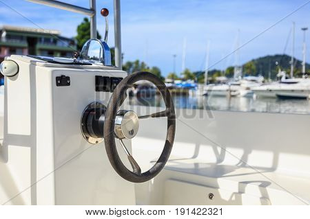 Black Steering Wheel On Speed Boat At Pier