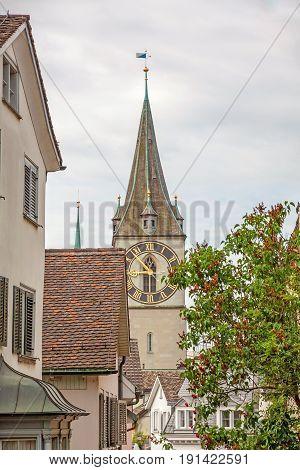 Church Saint Peter view through houses in downtown Zurich-