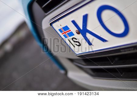 Detail of an Icelandic flag in the corner of license plate placed at the front of a vehicle