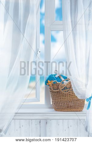Beach basket filled with towels sitting in open window overlooking the ocean