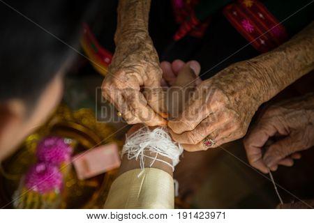 Wrist band with white thread at wedding, ritual, Thai dress.