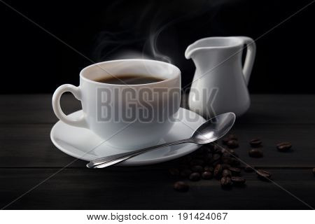 Cup of hot coffee with coffee beans and saucer on a wood table. Dark background