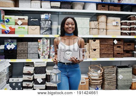 Portrait Of A Beautiful African American Woman Holding Home Sign And A Sconce Torch In The Store.