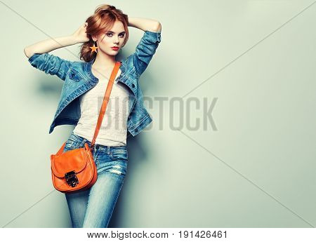 Fashion portrait of beautiful young woman with red hair. Girl in blouse and jeans. Jewelry and hairstyle. Girl with handbag poster