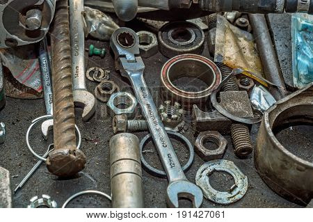 Old nuts, bolts, screws and instruments at car repair shop