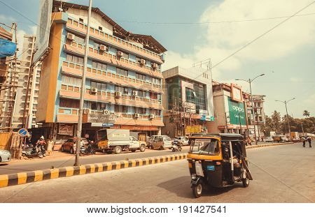 MANGALORE, INDIA - FEB 24, 2017: Rickshaw driving past colorful modern buildings on indian street on February 24, 2017. With population of 500,000 Mangalore is chief port city of Karnataka state