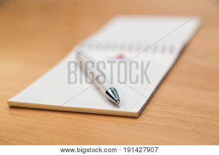 A notebook and ballpoint pen lying on a wooden table.