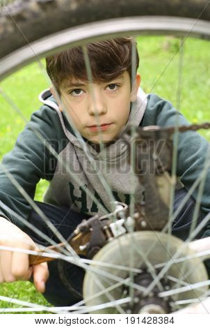 teenager boy repair tire on bicycle close up summer outdoor photo