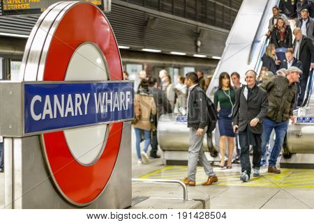 Canary Wharf Underground Sign With A Crowd Of Commuters Coming Down On An Escalator In The Backgroun